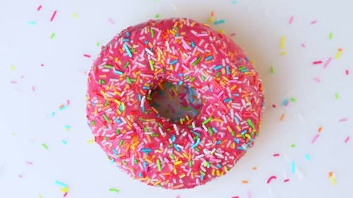 Delicious Sweet Donut Rotating on a Plate. Top View. Bright and Colorful Sprinkled Donut Close-up