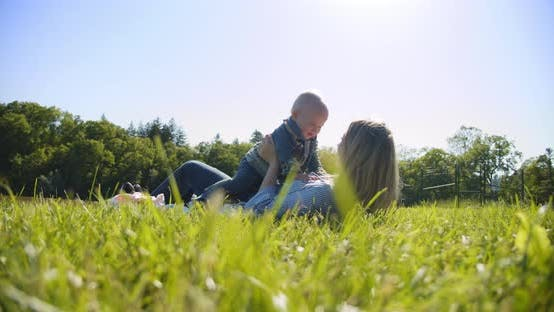 Beautiful Woman Lay Down on the Grass and Lifts the Child Up Smiling. Slow Motion