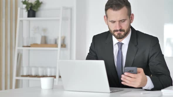 Thumbnail for Businessman Using Smartphone and Laptop at Work