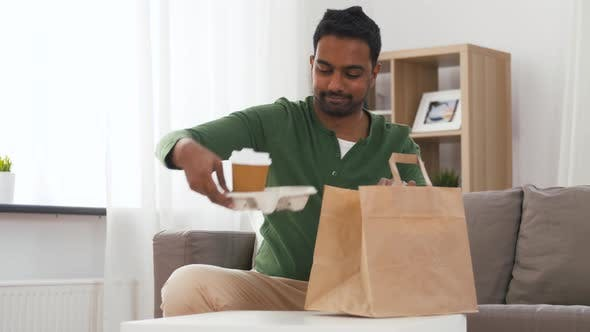 Thumbnail for Indian Man with Takeaway Coffee and Food at Home
