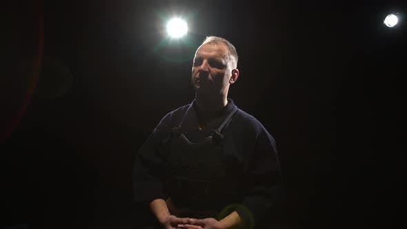 Thumbnail for Kendo Guru Sitting on Floor with Closed Eyes at Background Spotlights