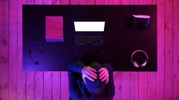 Thumbnail for Trauriger Gamer sitzt zu Hause hinter dem Computer und weint