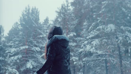 Woman Walks Through the Woods in Winter