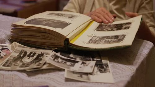 Old Woman Is Looking at Old Photo Album at Home
