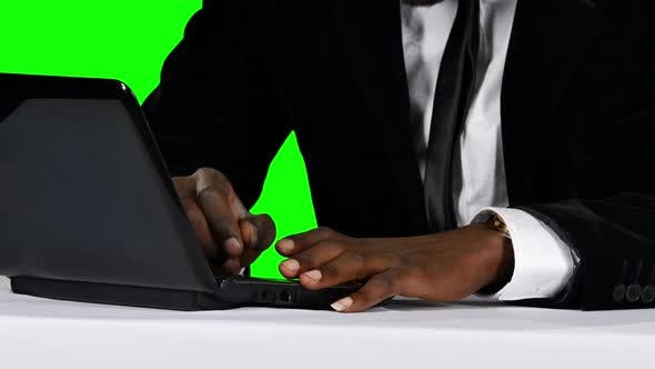 Cover Image for Young Businessman Working on His Laptop at His Desk. Green Screen