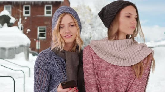 Cover Image for Two girls dressed for winter using smartphone outside in snowy neighborhood