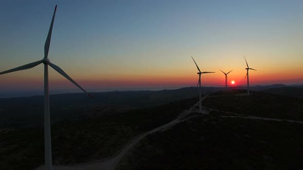 Thumbnail for Aerial view of slowly rotating windmill blades at colorful sunset