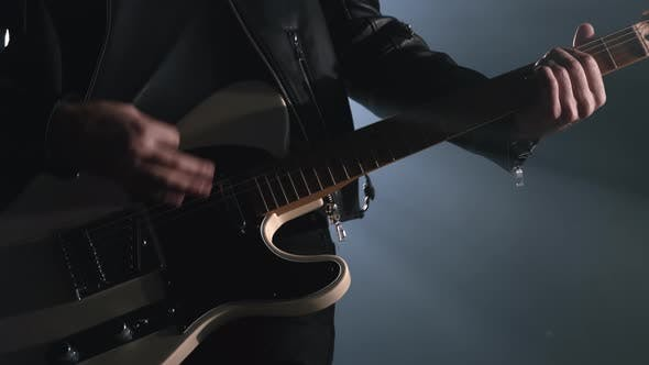 Thumbnail for Rock Musician Man in Smoky Studio, on Stage Masterfully Playing Electric Guitar