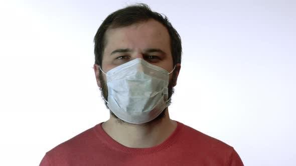 Thumbnail for Man Removes Medical Mask Against Coronavirus, Smiles at Camera. End of Epidemic