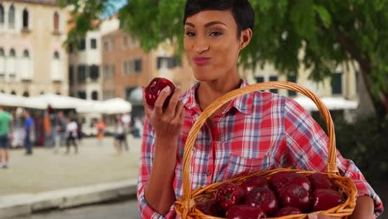 Portrait of healthy attractive black female biting into juicy apple