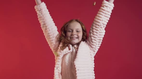 Thumbnail for Cute Smiling Girl with Long Hair Scattering Gold Confetti on Red Wall