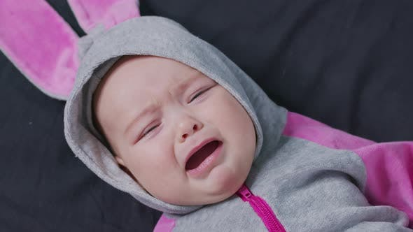 Thumbnail for A Baby Lies on the Bed and Cries. Child Is Upset and Crying.