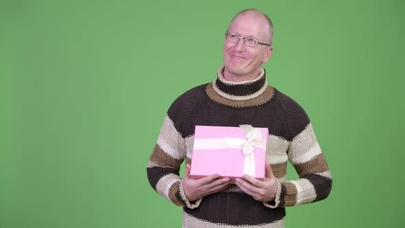 Thumbnail for Happy Mature Bald Man Thinking While Holding Gift Box
