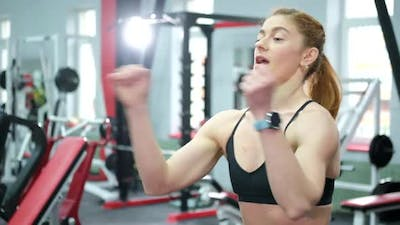 Fitness a Muscular Female Athlete Trains in the Gym with Heavy Dumbbells