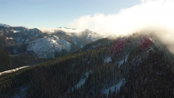 Flying Helicopter View Snowy Mountain Range Sun Backlit Clouds Evergrenn Forest