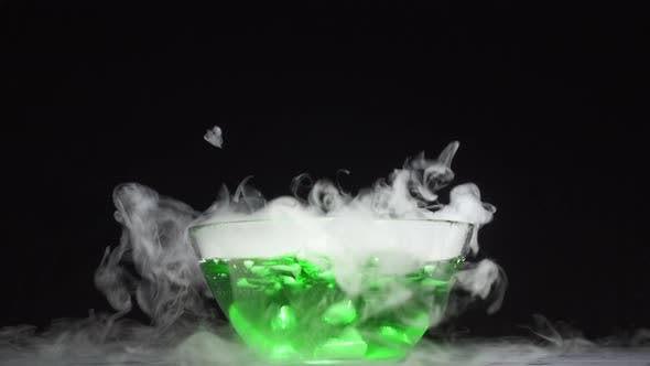 Green Liquid Boils Giving Off Smoke in a Glass Bowl on a Black Background