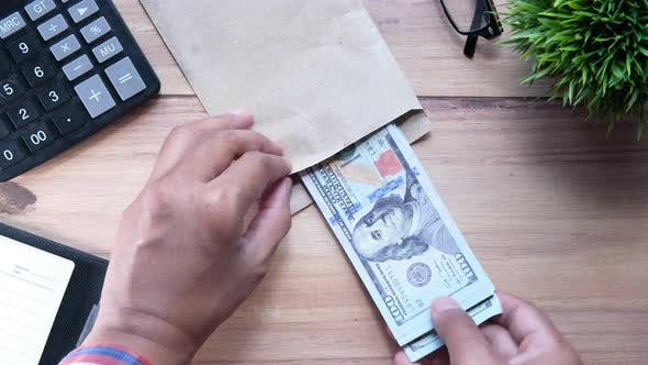 Thumbnail for Person Hand Putting Cash in a Envelope.