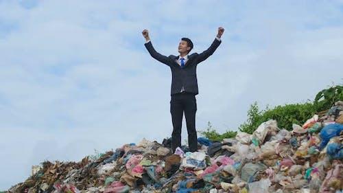 Le bonheur de l'homme d'affaires sur la pile des ordures