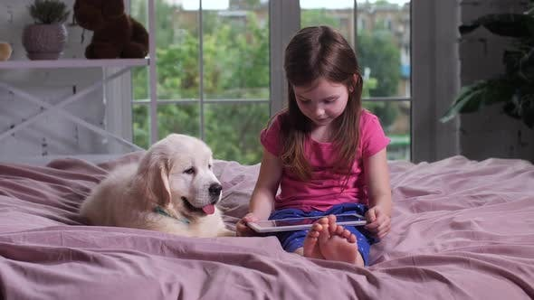 Thumbnail for Cute Child Watching Video with Puppy on Bed
