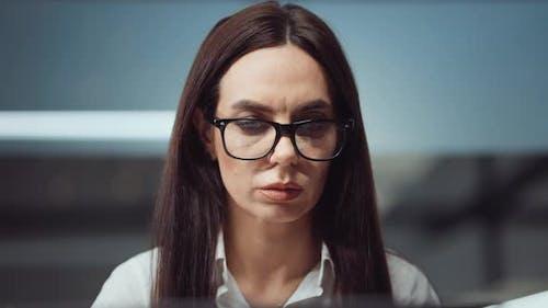 Businesswoman in eyeglasses working in office