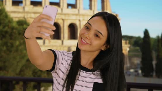 Thumbnail for Latin female near Coliseum taking selfies to share with friend on social media