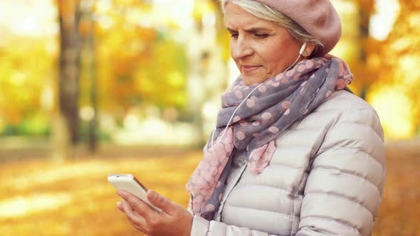Thumbnail for Old Woman with Smartphone and Earphones in Autumn 19
