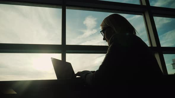 Thumbnail for Frau in Business Anzug Arbeiten mit Laptop im großen Bürofenster