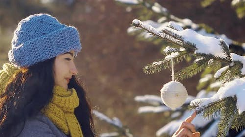 Woman Decorates Fir-tree with Toy During New Year in Forest