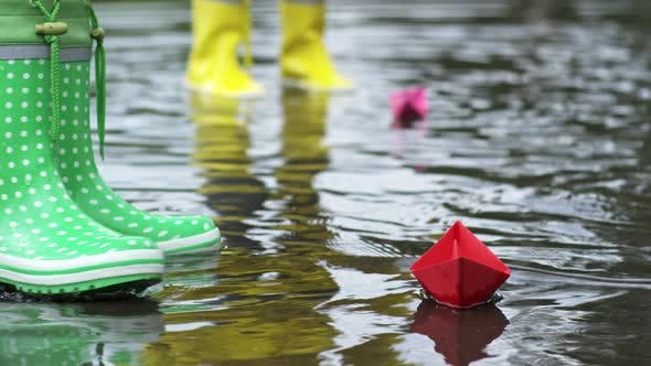 Thumbnail for Girl Putting Paper Boat in Puddle