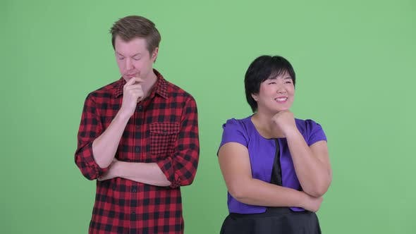 Thumbnail for Happy Overweight Asian Woman with Stressed Scandinavian Hipster Man Thinking Together
