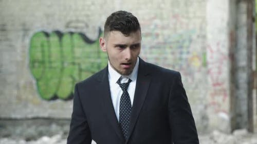 Man in Suit Corrects Necktie Looks Around and Flees at Ruins