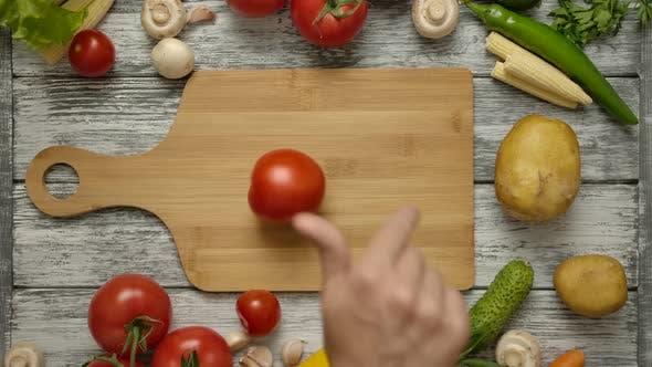 Thumbnail for Männliche Hand wirbelnde Tomate auf Schneidebrett.