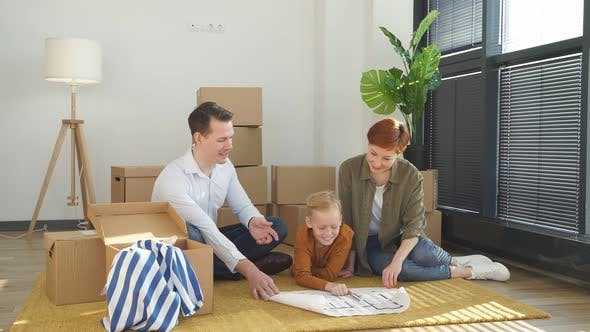 Friendly Family With Child Boy Sit On Floor Talking Planning Their Home Interior Moving Into New