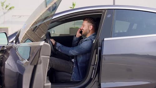 Likable Smiling Young Modern Bearded Man Talking on Phone in a Luxurious Car