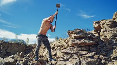 Strong man is training with heavy hammer