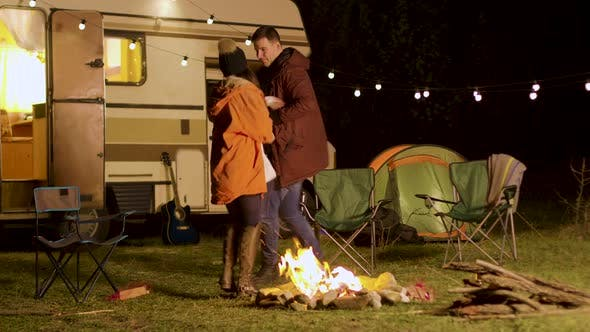 Thumbnail for Cheerful Young Couple Dancing Around Camp Fire in Cold Night of Autumn