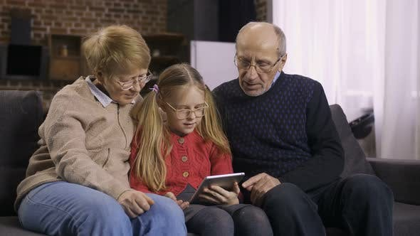 Thumbnail for Teen Girl Teaching Grandparents To Use Touchpad