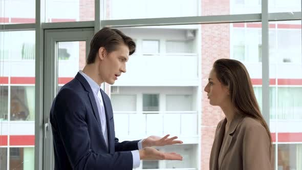 Angry colleagues arguing shouting at stressed sad female employee at meeting