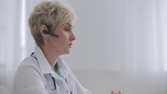 Consultation of Doctor By Telephone, Female Physician Is Answering on Questions of Patients in Call