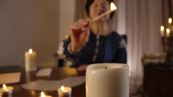 Thumbnail for Big White Candle Standing at the Foreground As Blurred Old Caucasian Woman Lighting Up Candles