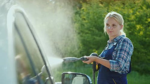 Active Middle-aged Woman Washes Her Car in the Backyard of the House