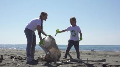 Family Picks Up Trash From the Beach in Trash Bags
