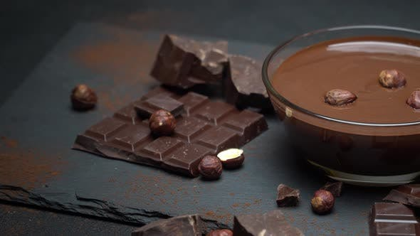 Cover Image for Glass Bowl of Chocolate Cream or Melted Chocolate, Pieces of Chocolate and Hazelnuts