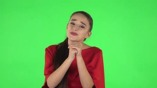 Porträt von Pretty Young Woman hält Palm zusammen und fragt nach etwas. Grüner Bildschirm