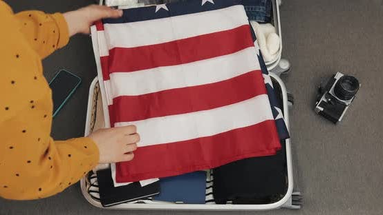 Thumbnail for Woman's Hands Puts an American Flag in a Suitcase. Traveler Girl Packing Suitcase for a Journey on