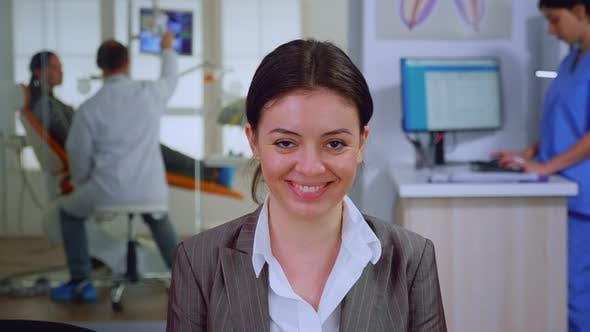 Porträt eines lächelnden jungen Patienten, der auf dem Stuhl auf der Webcam sucht
