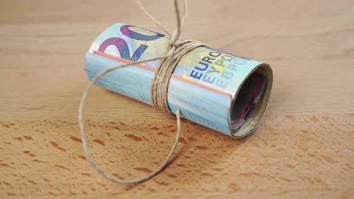 Ein Bündel Euro-Währungsbanknoten mit gebundenem Seil geht unter