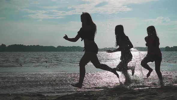 Thumbnail for Teenagers Happily Run Along the River Bank