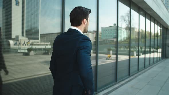 Thumbnail for Back View Businessman Walking with Phone. Man Using Smartphone Outdoors