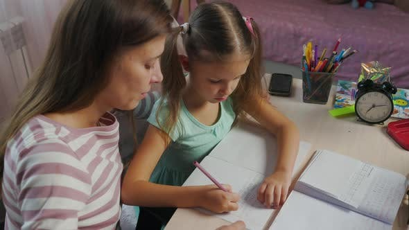 Mother And Daughter Doing Homework From School Together
